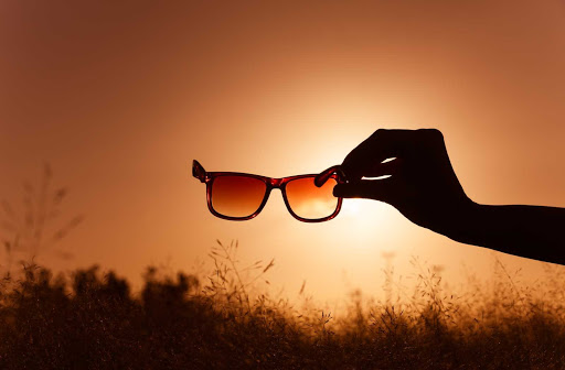 silhouette of a hand eclipsing late eveinng sunlight, holding sunglasses facing the viewer