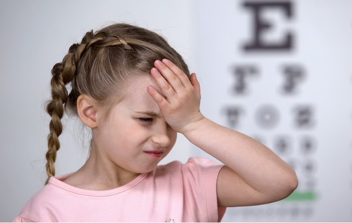 A little girl in front of a blurred eye test chart holding her head because of a headache due to myopia